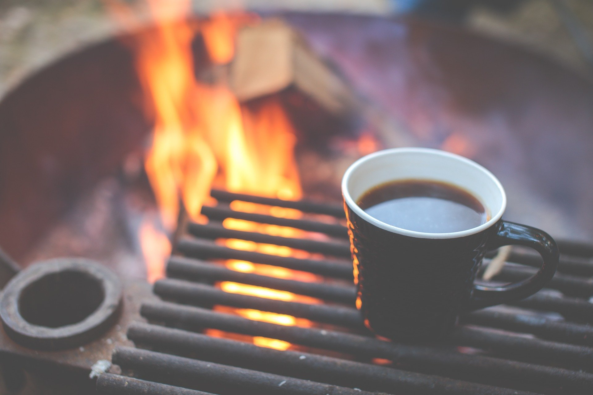 photo of a coffee mug safely placed on a grill within a burning campfire
